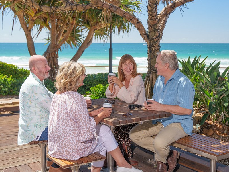Group of over 50s sitting at picnic table overlooking the beach - Ingenia Lifestyle Nature's Edge